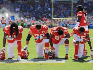 Dozens of athletes kneel during national anthem